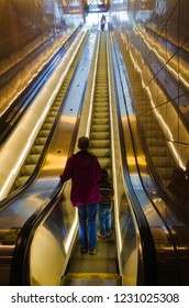 A mother and her young child begin to ride up an escalator.