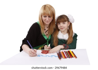Mother and her young daughter drawing together, set of felt tips on the table. Schoolgirl is  drawing  in pencil. Woman is painting the picture. Isolated over white background.
