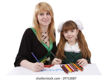 Mother and her young daughter drawing together, set of felt tips on the table.Girl is painting her family in bright colours.  Isolated over white background.