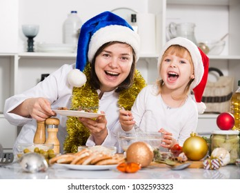 Mother and her young daughter are satisfied of dish for New Year at home.