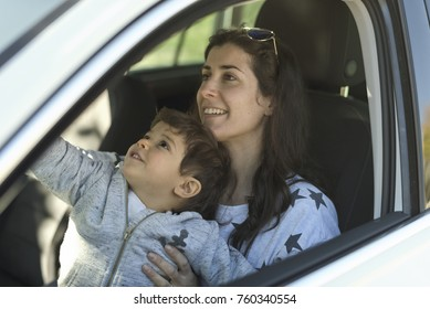 Mother with his little son inside a car parking