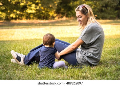 a mother and his newborn baby son sitting in the grass at the park spending time with family in a garden