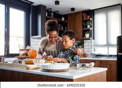 Mother with his son prepare pie in the kitchen