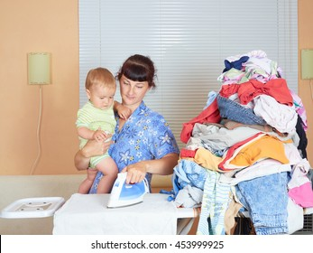 Mother holding baby in arm, ironing with the other arm. In a room near the window.