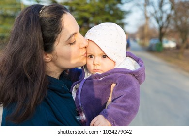 Mother holding a baby daughter in hands outdoors, kissing her.