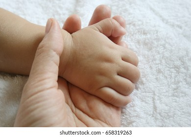 Mother holding baby hand