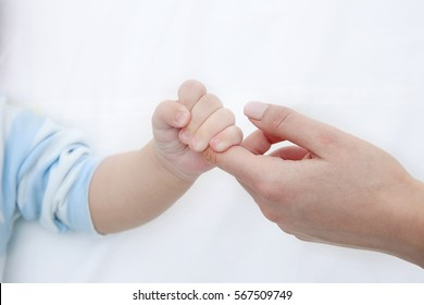 Mother holding baby hand, closeup