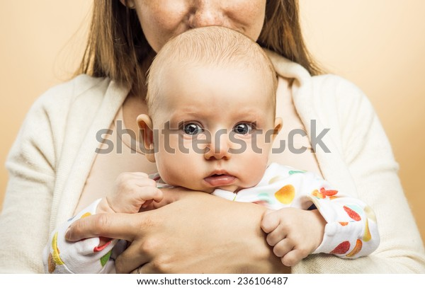 Mother holding a baby in her arms and kissing it studio shot on beige background