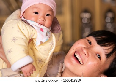 The mother holding the baby laughed heartily