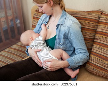 Mother holding the baby on the hands  and breastfeeding him