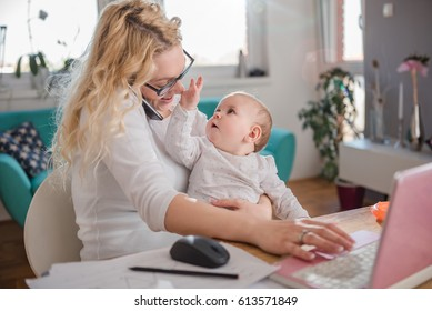 Mother holding baby, talking on smart phone at home office and using laptop