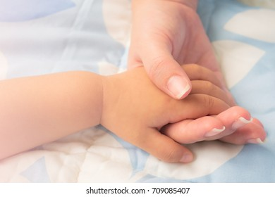 Mother holding baby's hand. Mother's love.