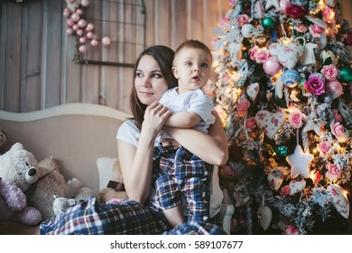 mother holding a child at the Christmas tree