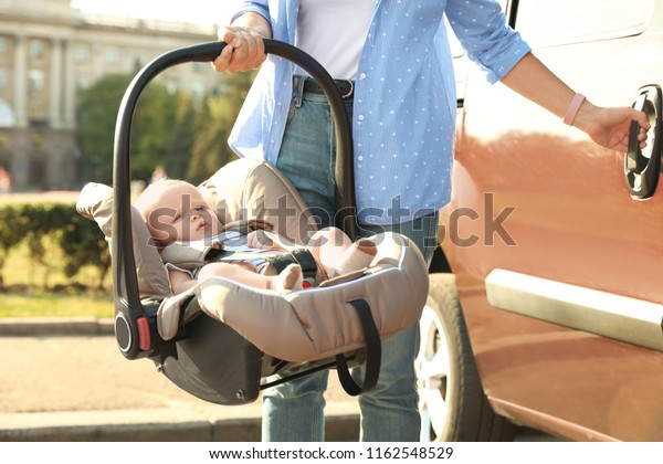 Mother holding child safety seat with baby near car outdoors