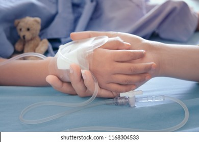 Mother holding child's hand who fever patients in hospital to give encouragement.