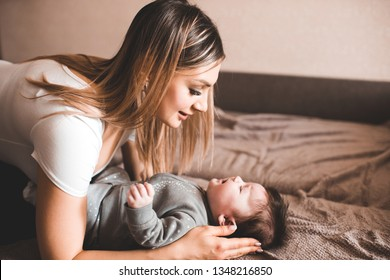Mother holding crying baby lying in bed in room. Unhappy child. Looking at each other. Motherhood.