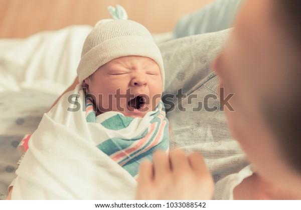 Mutter, die einen süßen Neugeborenen in den Armen hält. Schlampiges Baby gähnt.