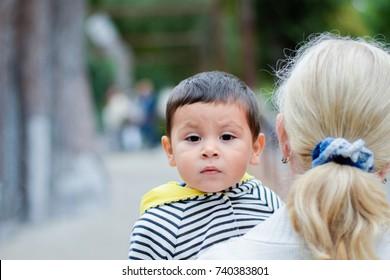 Mother holding cute sad little boy