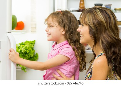 Mother holding up daughter in modern kitchen opening fridge door looking inside happily.