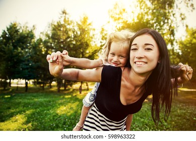 Mother holding daughter outdoors smiling. Happy mother and daughter walking in the park