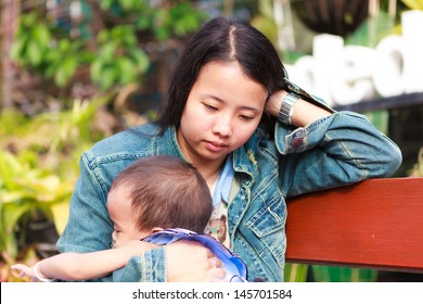 Mother holding daughter sitting on wooden bench in park