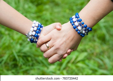 Mother holding daughter's hand. They both wear equal sea style handmade bracelets.