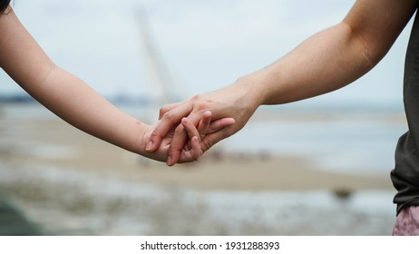 Mother holding daughter's hand walking by the sea believes family concept.