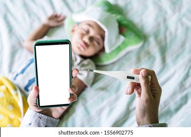 Mother holding a digital thermometer and smartphone to checking for her son sickness, illness, and fever flu while baby is slepping on a bed with wet cloth on his forehead. White background screen.
