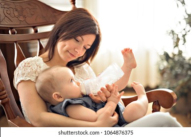Mother holding and feed her baby child on chair