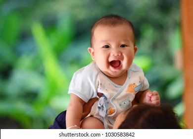 Mother holding funny adorable baby boy and play with her son.