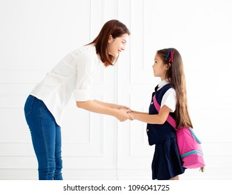 Mother holding hand of daughter ready go to school