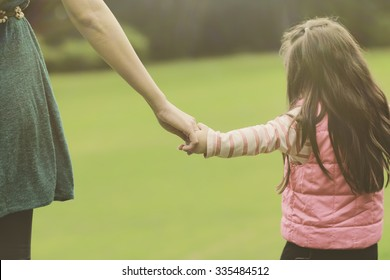 Mother holding a hand of her daughter in summer day outdoors