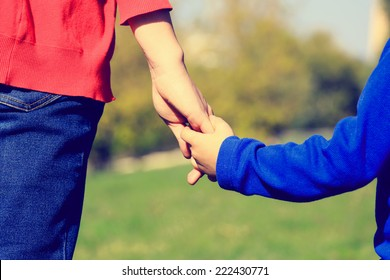 Mother holding hand of her son outdoors