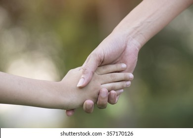 Mother holding a hand of his son in summer day