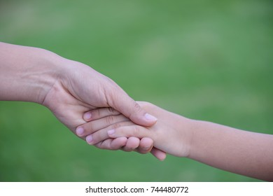 Mother holding a hand of his son with green glass background. Love , famiy and mother day concept.