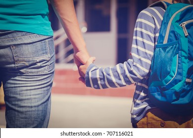 Mother holding hand of little son with backpack
