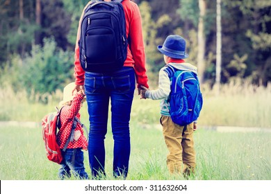 Mother holding hands of two kids with backpack going to school or daycare