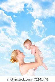 A mother is holding up her baby against a bright blue sky of clouds. Add your text to the empty copyspace.