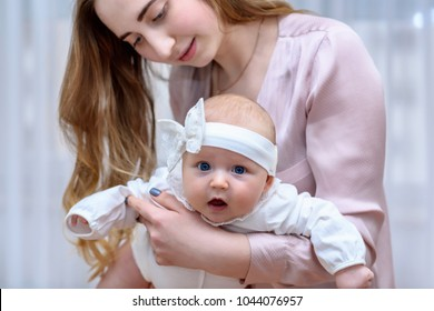 Mother holding her baby girl. Cute toddler portrait
