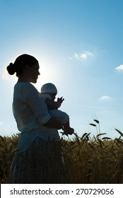 mother holding her baby on a wheat filed, silhouette