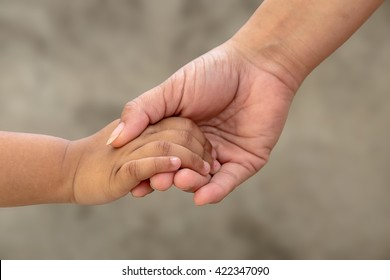 Mother holding her child hands close-up