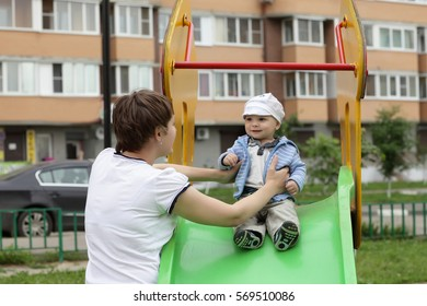 Mother holding her child on a slide at playground