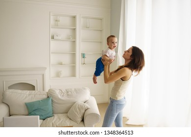 Mother holding her child. Woman and infant boy relax and playing in living room. Family, maternity, tenderness, parenthood, responsibility and love concept