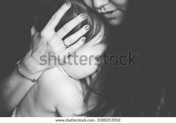 Mother holding her crying little baby. black and white photo. pain with teething