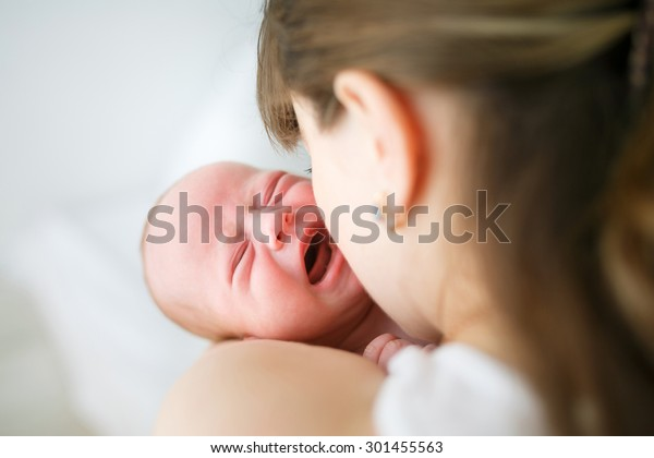 Mother holding her crying little son in studio