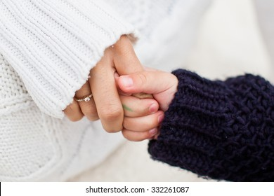 Mother holding her daughter hand. Daughter holding mom's finger. Both in warm and cozy sweaters. Daughter in blue sweater and mother in white sweater. Conceptual photo of diversity and family