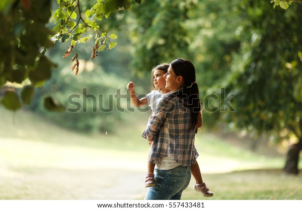 Mother holding her daughter and playing around the park on beautiful morning.