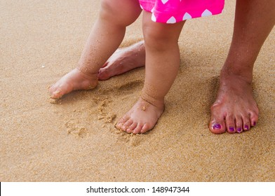 Mother holding her daughter at sandy beach