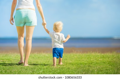 Mother holding her little boys hand walking outdoors at a beach park.