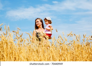 Mother holding her lovely daughter in wheat